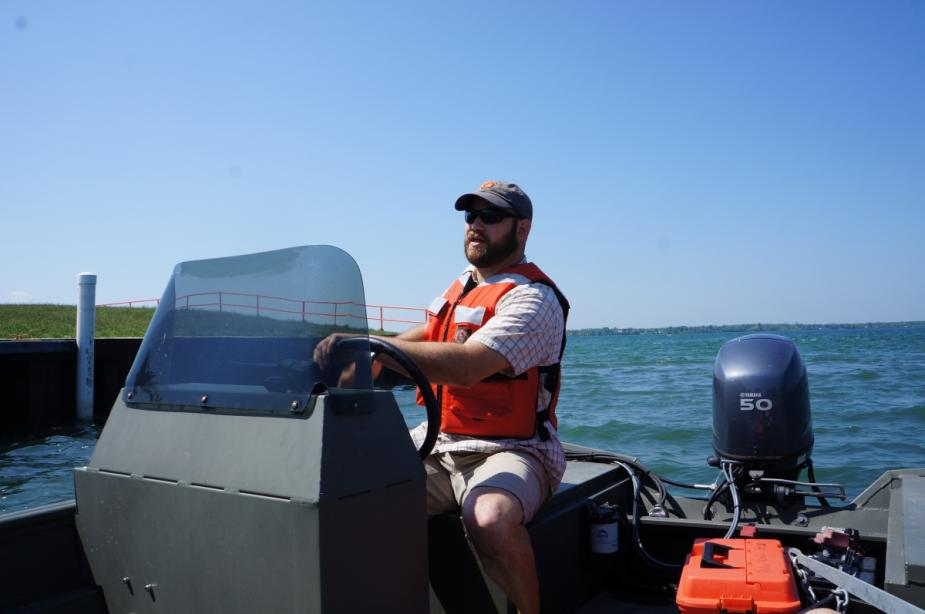 A person sits at the controls of a boat near a wall.