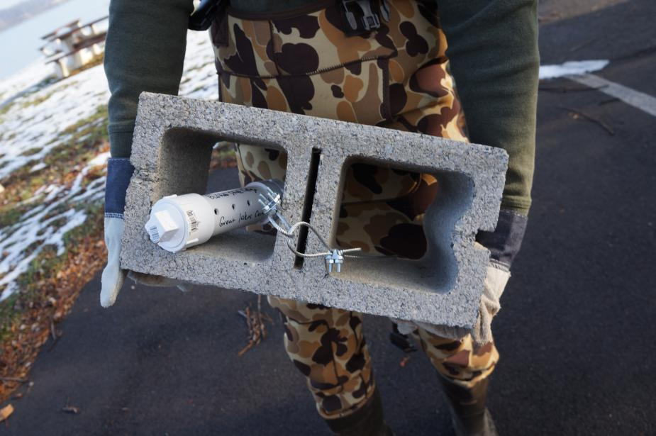 A person holds a cinderblock with a PVC tube strapped inside it.