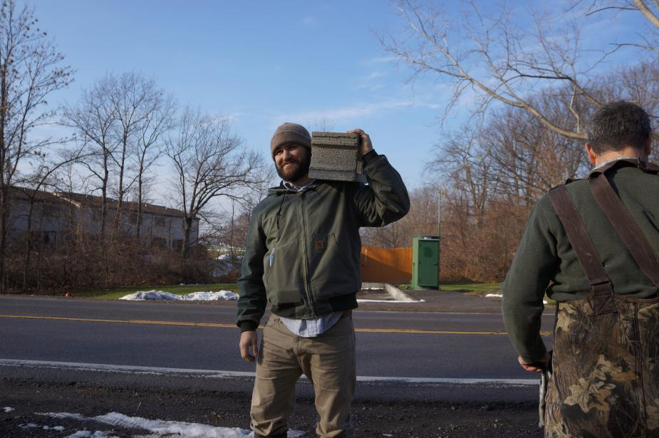 Two people by the side of a road, one holding a cinderblock on their shoulder.