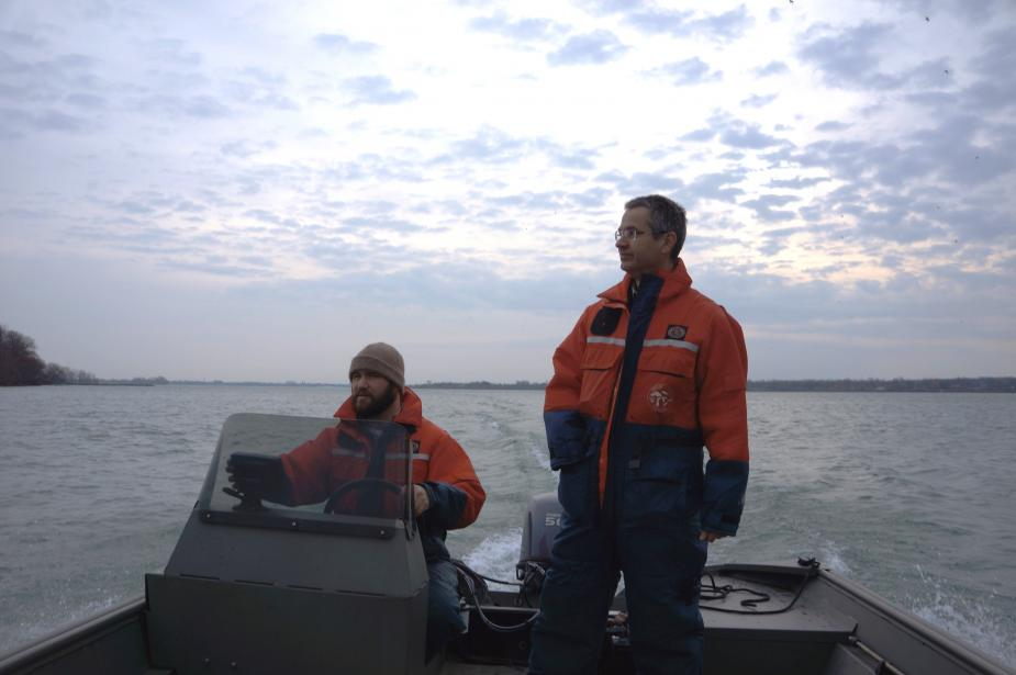 Two people in flotation suits are on a boat. One is standing and the other sitting at the controls.