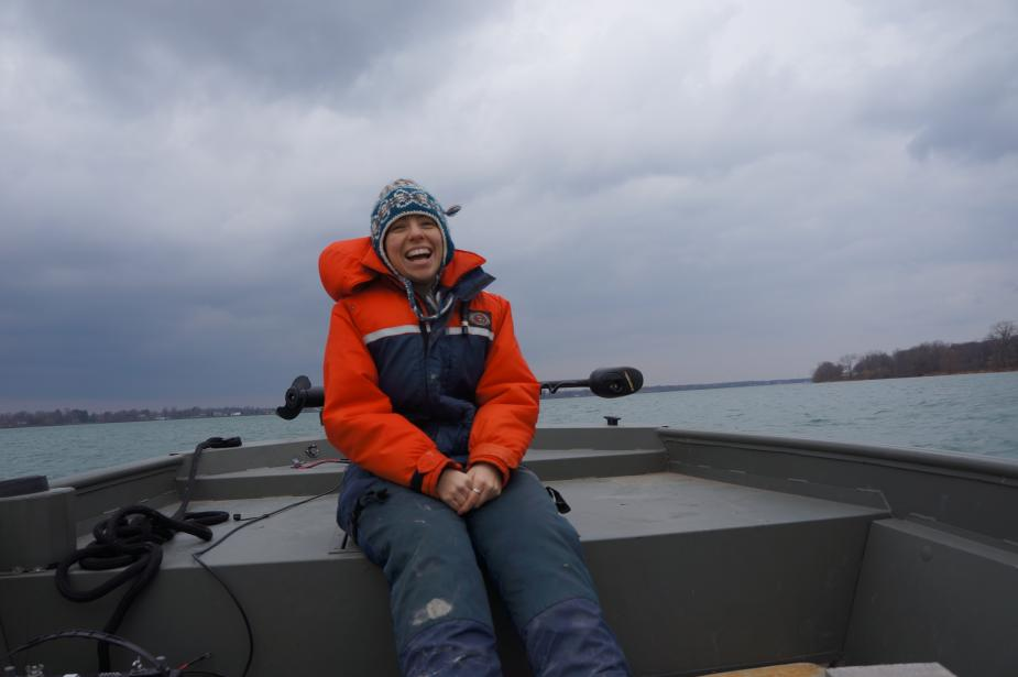 A person in a float suit and a knit cap sits at the front of a boat. The sky is cloudy.
