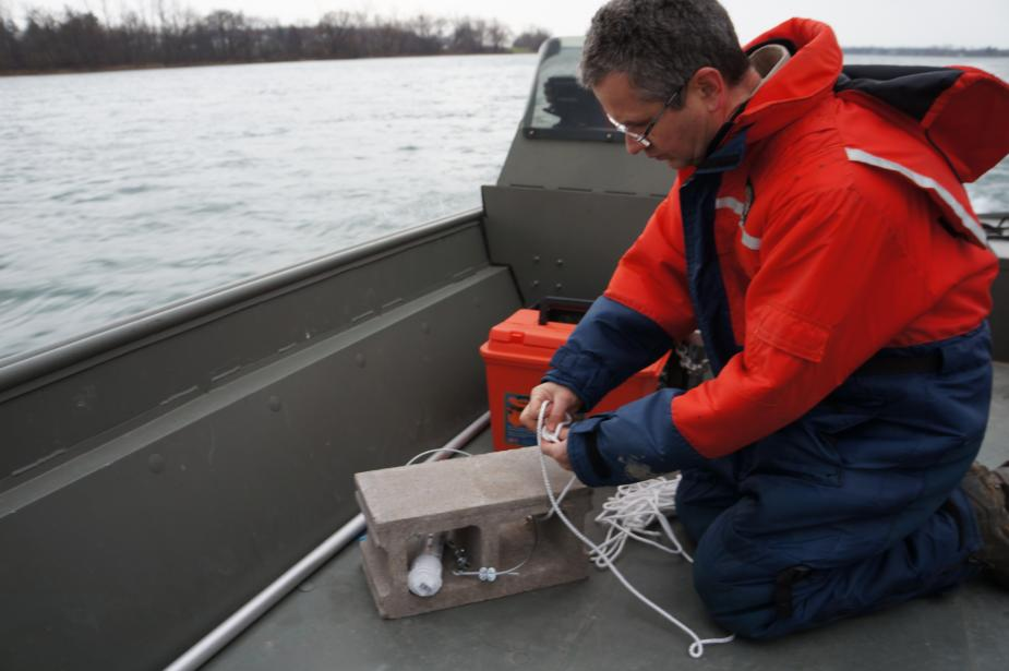 A person in a float suit kneels on a boat, tying a narrow rope around a cinderblock.