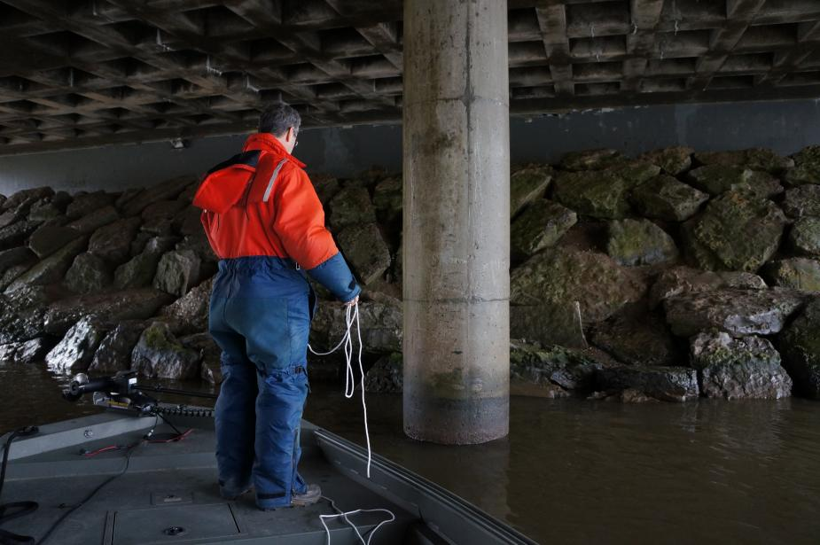 A person in a flotation suit stands on a boat under a bridge. There are rocks on the shore leading up to the bridge and a concrete pillar.