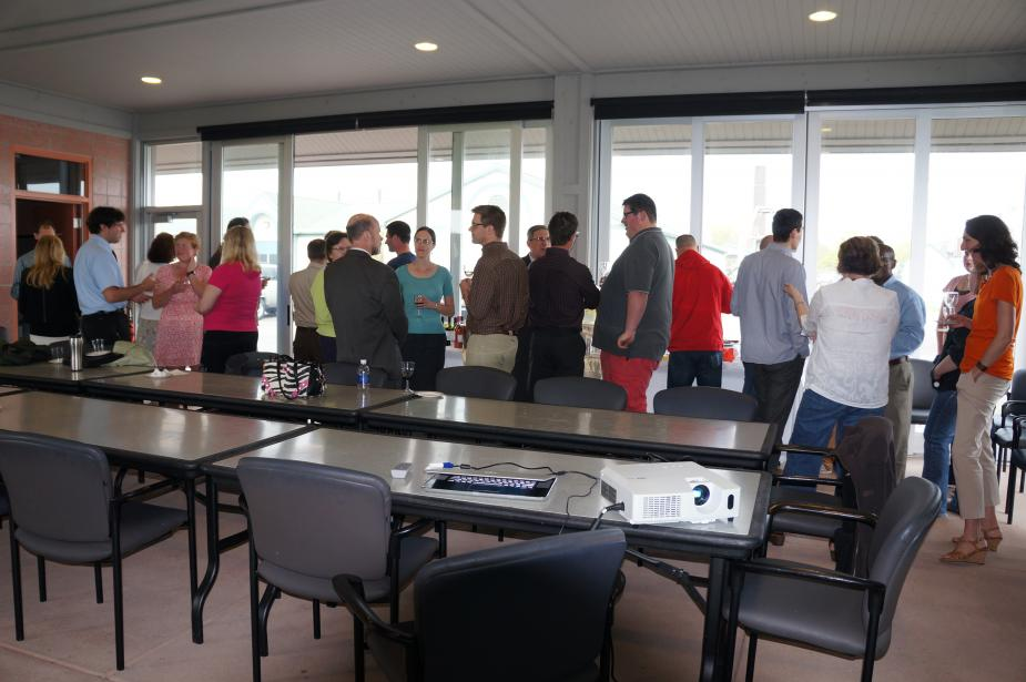 People standing and talking in a pavilion with tall glass windows all along one side. There is a table in the front of the picture with a projector set up on it.