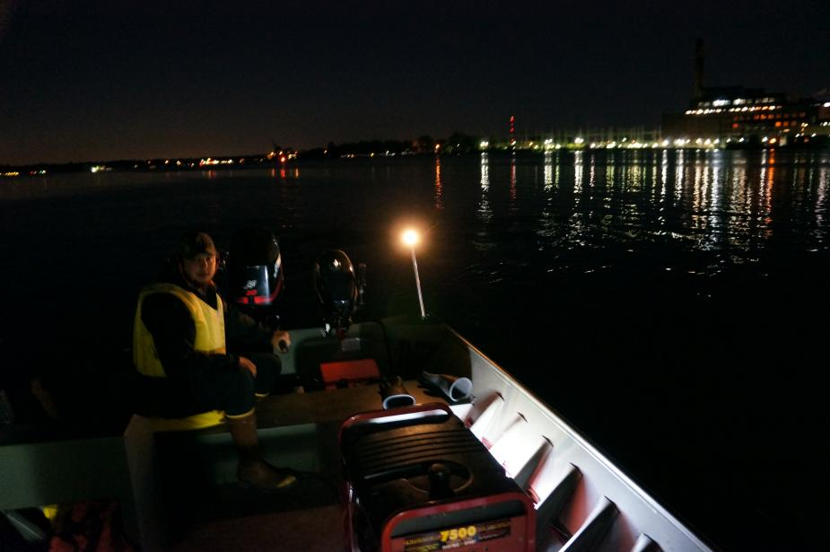 Nighttime picture of a person sitting in the back of a boat running the engine.