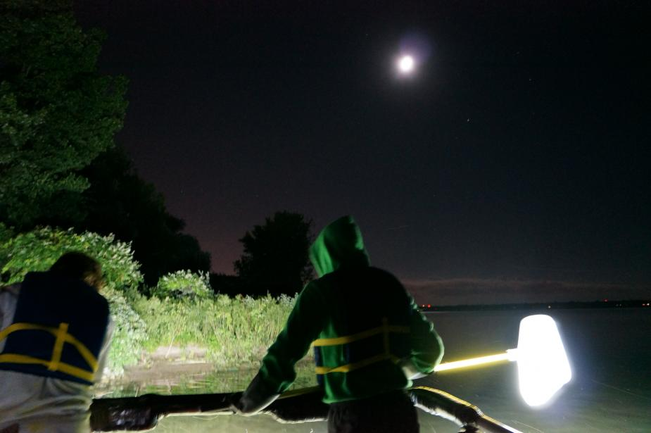 Two people standing on a boat at nighttime, one holding a net on a long pole. The moon is out.