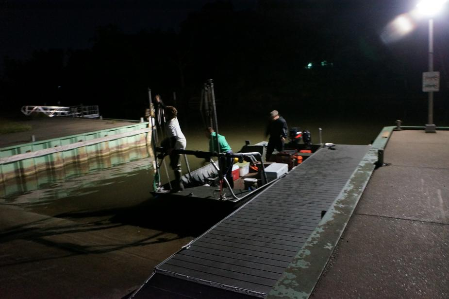 Nighttime picture of a boat sitting in the water at a boat launch. Three people are on board.