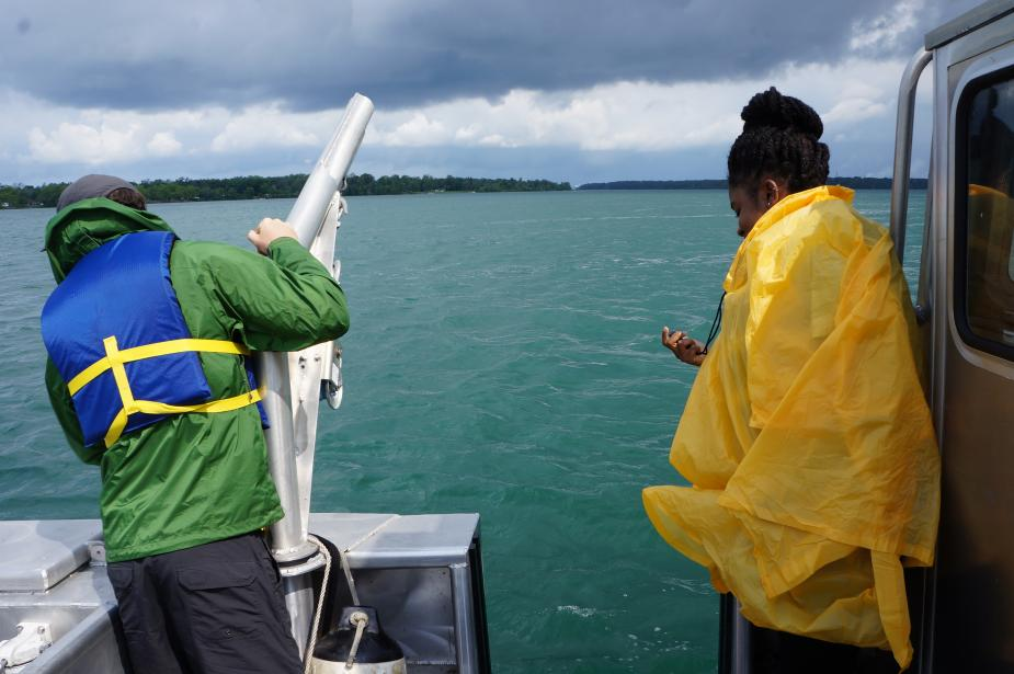 Two people in rain gear stand by the edge of the boat. One is near a winch and the other has a stopwatch