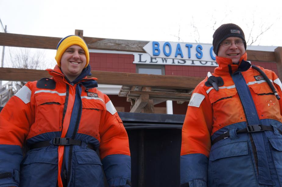 two people in flotation suits and knit caps stand in front of a building with a sign