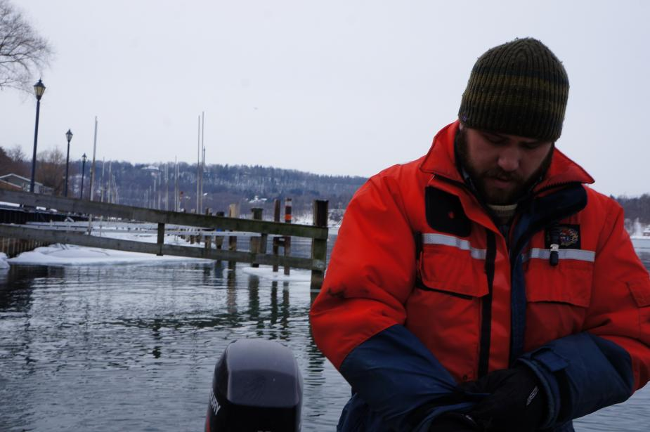 a person in a flotation suit and knit cap stands by the icy water