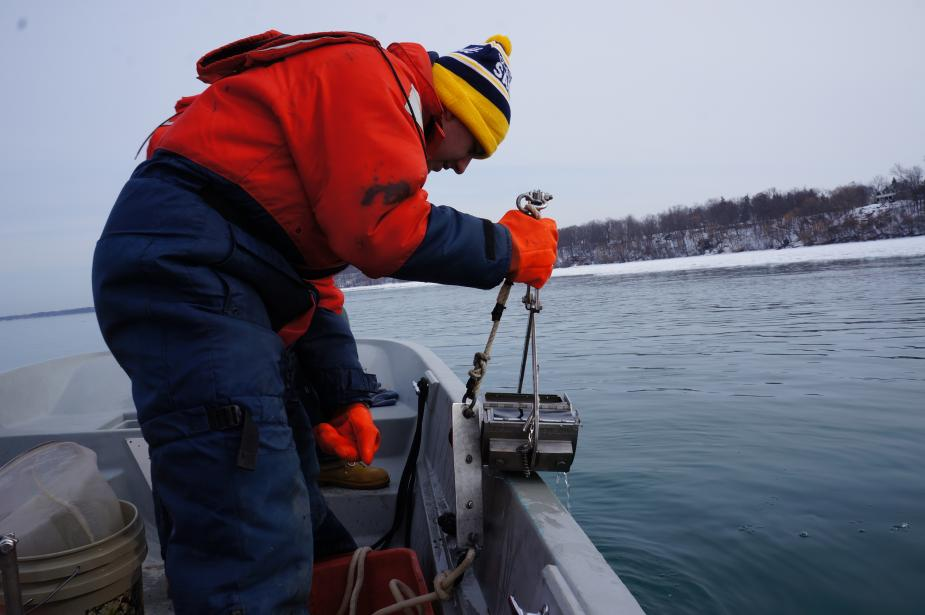 a person in a flotation suit, hat, and gloves holds a metal contraption on the edge of a boat in an icy river