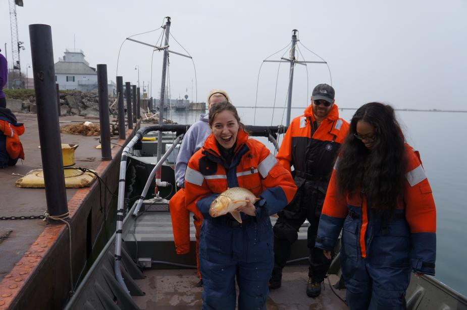A few people stand on a boat at dock. A different student holds up a mostly white fish