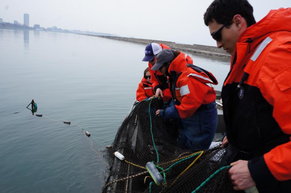 Students pulling black netting onto a boat