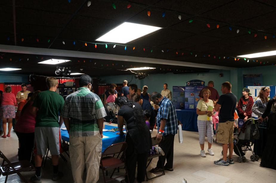 Groups of people visiting different display tables in a room.