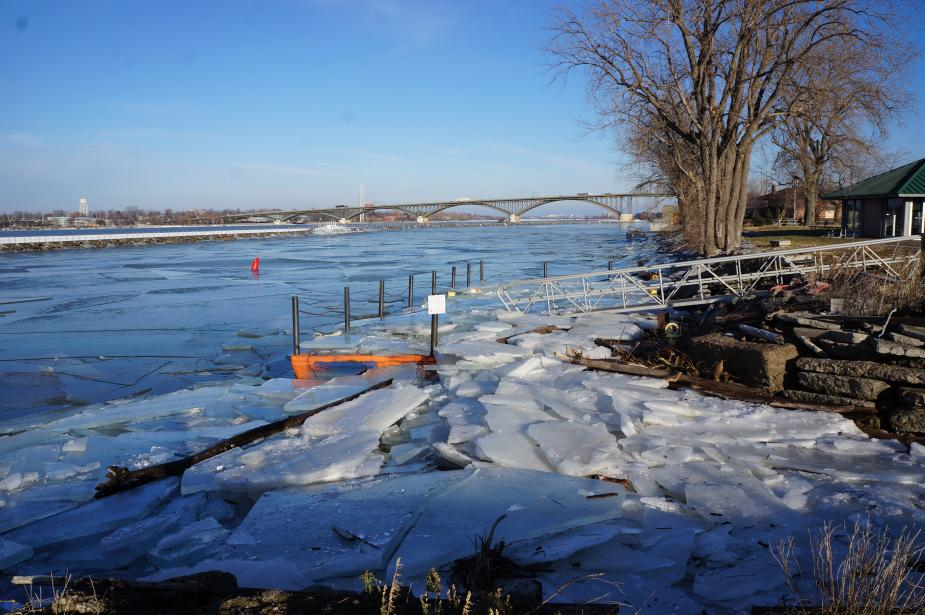 A boat dock covered with broken sheets of ice.