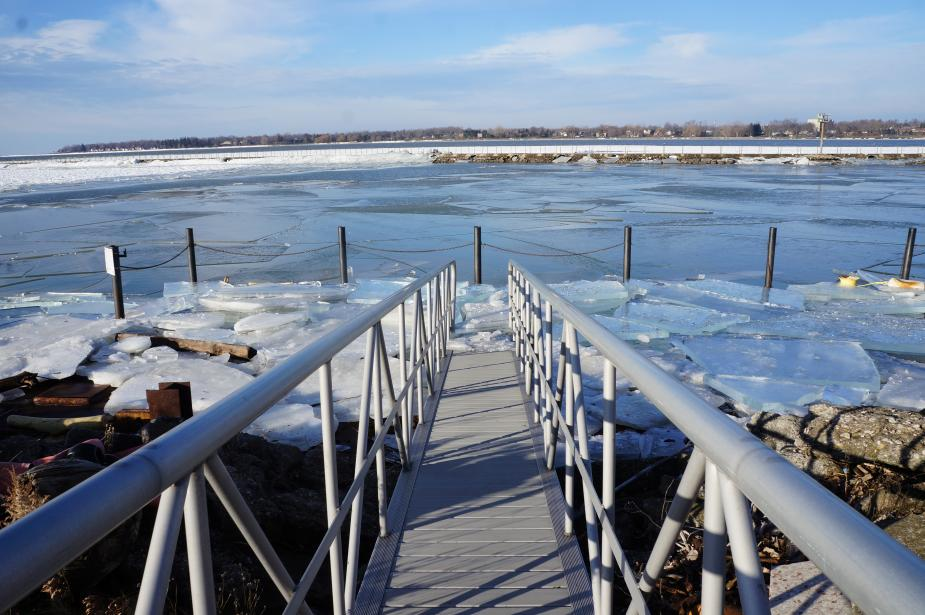 A view down the gangway of a ramp to a dock that is covered in broken sheets of ice.