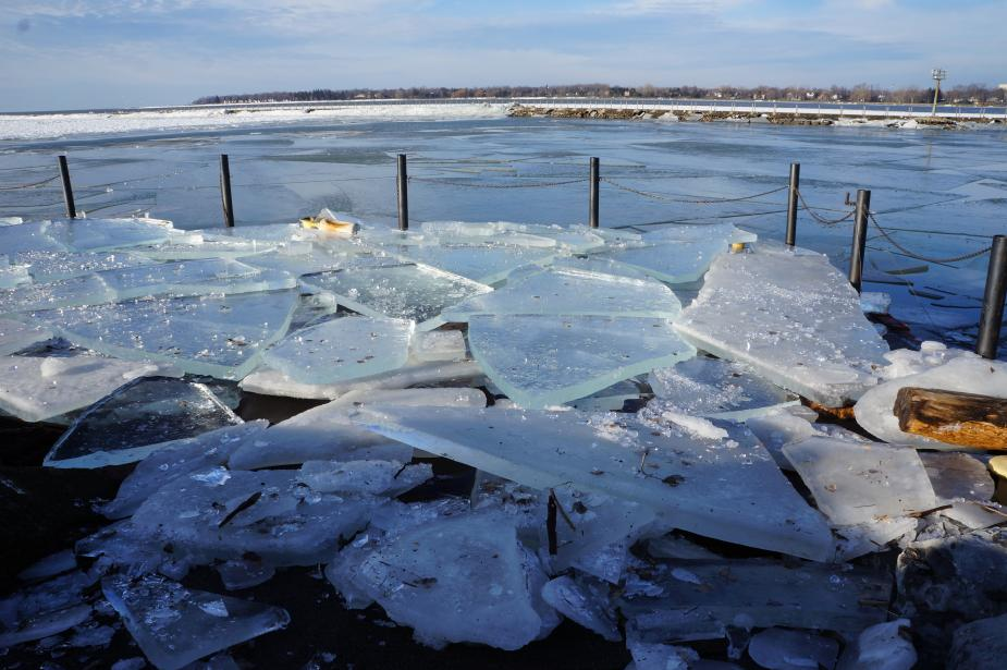 A boat dock covered with broken sheets of ice. Light sparkles in smaller pieces of ice. The sheets of ice are at least 4 inches thick.