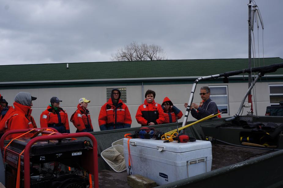Students in flotation suits stand behind a boat with a cooler and a generator on it. There is a white building with a green roof behind them.