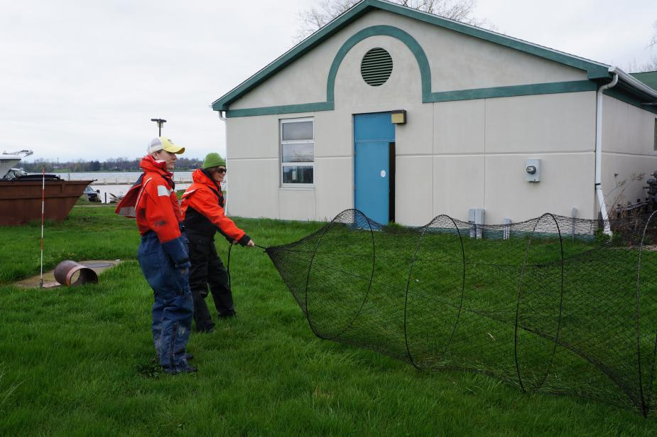 Two students in flotation suits hold a conical trap net open while standing on grass in front of a building.