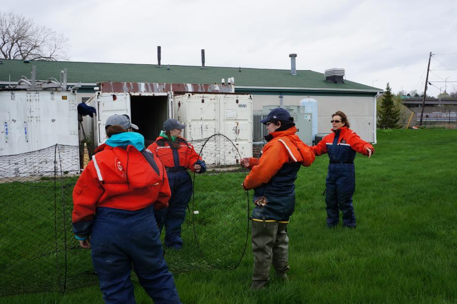 Three students in flotation suits hold a conical trap net open, while a fourth person gestures behind them, during an on-land demonstration. There is a building in the background.