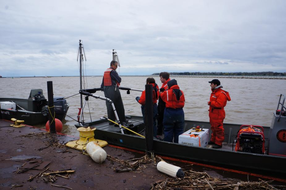 People in flotation suits stand on a flat boat tied up at dock. There is woody debris on the dock nearby. A second boat is tied up nearby.