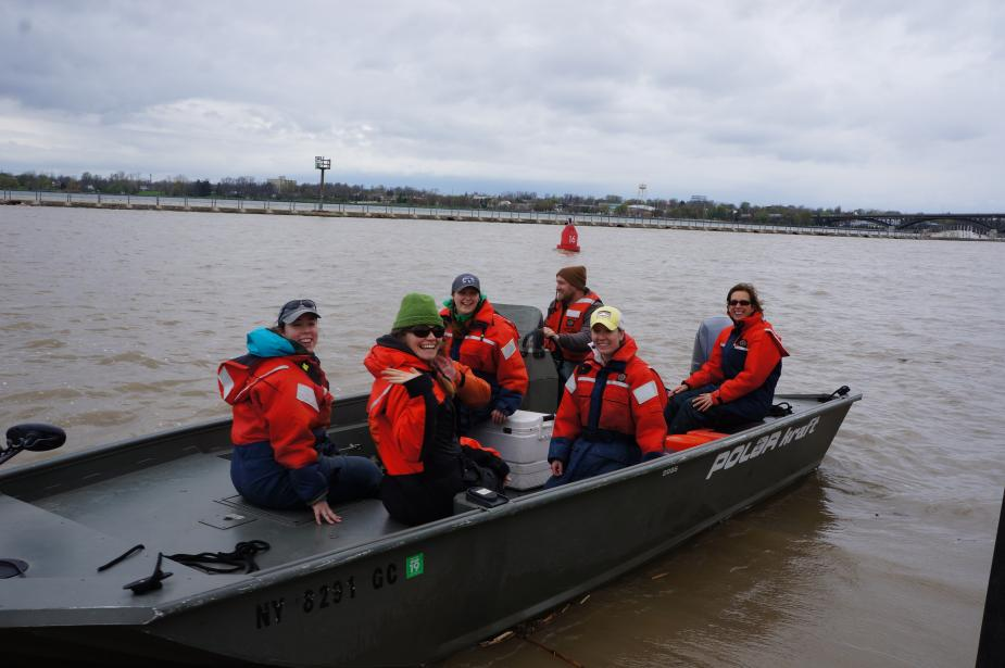 A shallow boat with people in flotation suits. A few people smile for the camera.