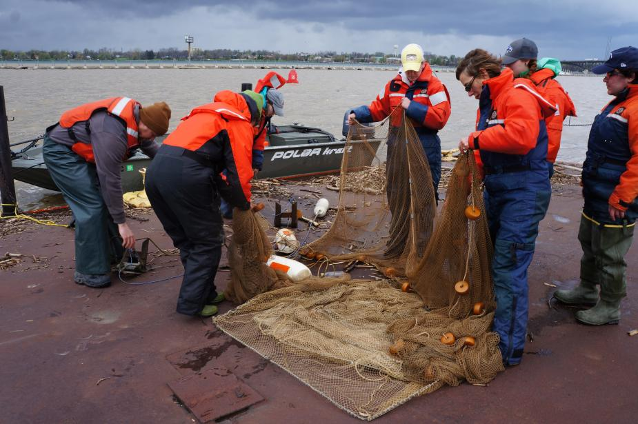 People in flotation suits laying out a large net on the dock.
