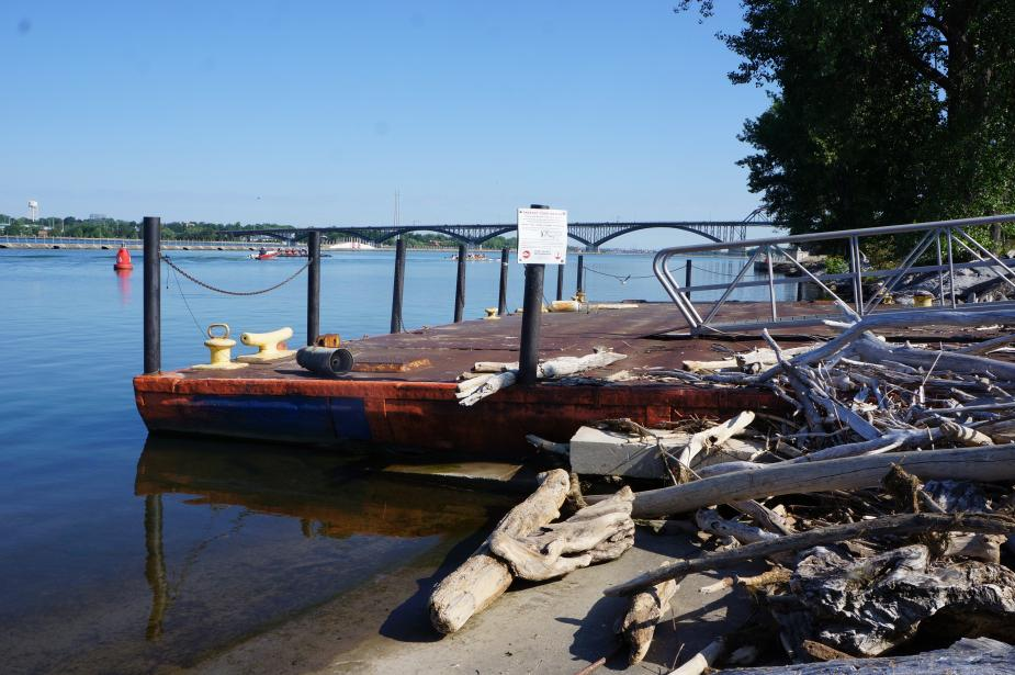 A dock made from a rusty sunken barge. Piles of driftwood sit on the concrete next to the dock.