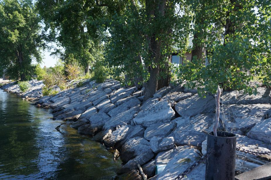 Neatly stacked stone slabs on the slope between the ground and the water, under a tree.