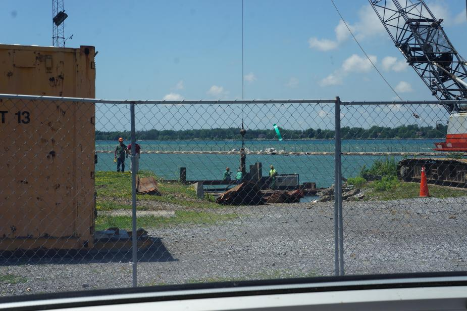 View of a construction site at the waterfront through a fence. A crane is lowering a steel beam down to some workers.