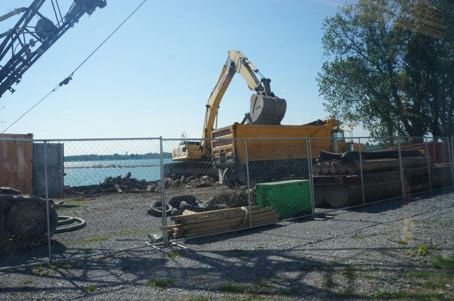 View of a construction site through a fence. An excavator is dumping debris into a dump truck.