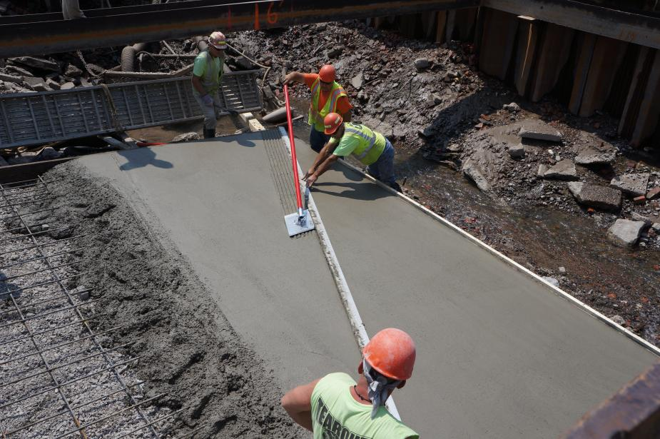Two workers at a construction site use a tool to put lines on fresh smooth cement.