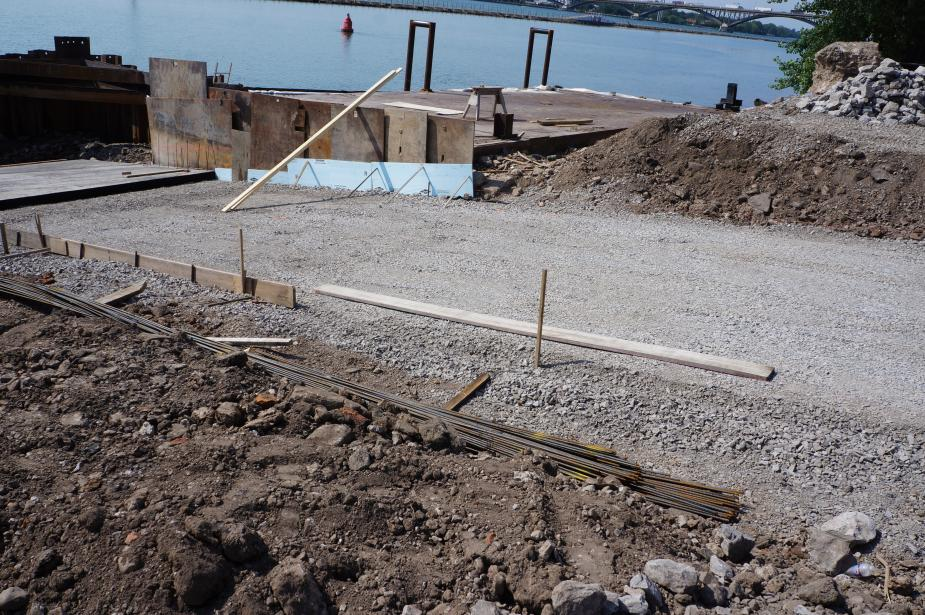 A driveway area in a construction site that is covered with gravel. Stakes are used along the edges of the driveway.