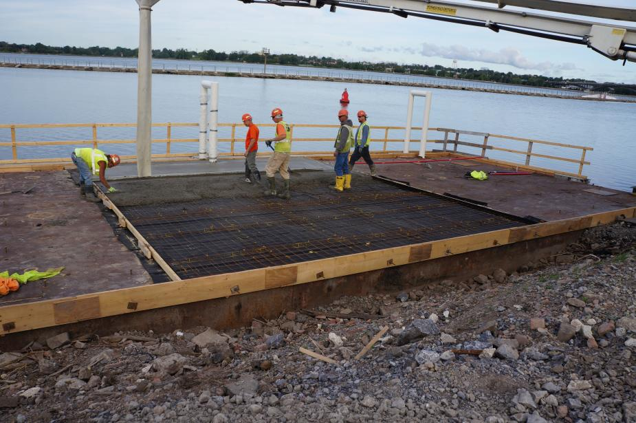 Construction workers spreading cement on a frame of rebar on top of a metal surface by the water.