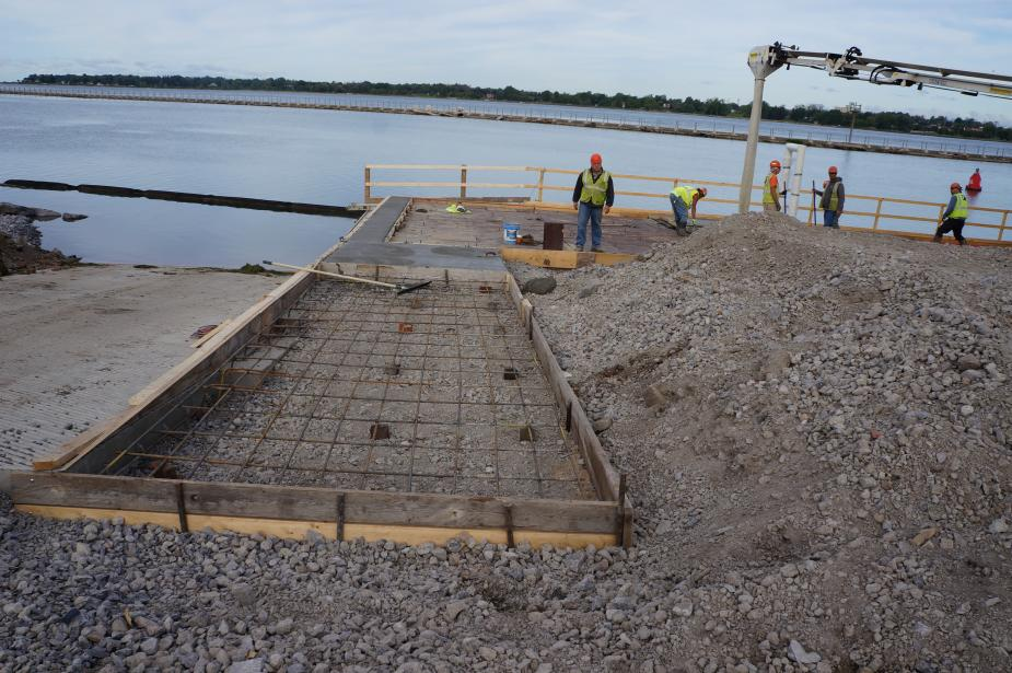 A construction site with workers by the waterfront. A frame with rebar and gravel goes down to a dock next to a boat ramp.