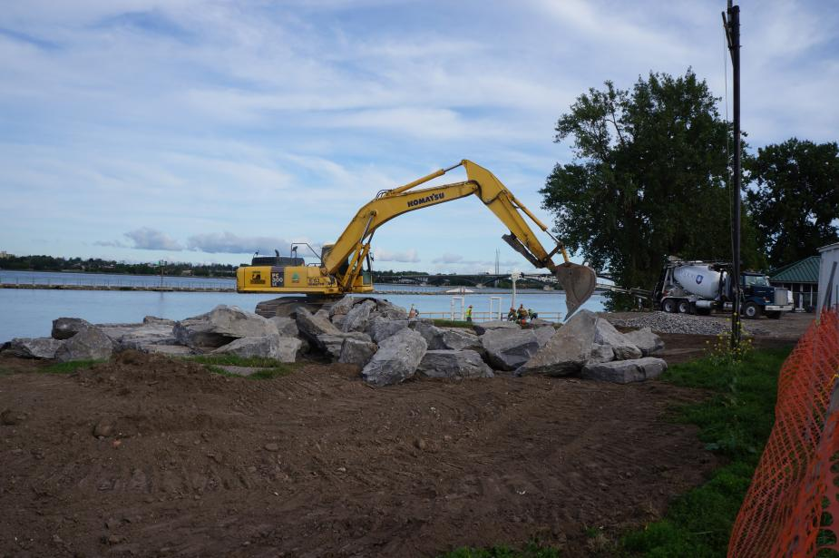 An excavator moves larges stones near the waterfront. A pile of large stones sits on the ground in front of the excavator.