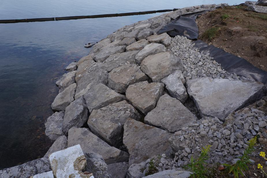 The slope down to the water is lined with evenly placed large stones.