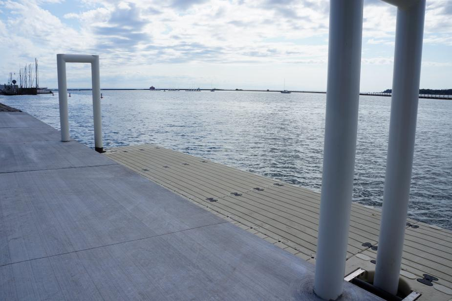 A concrete dock with two white metal u-shaped bars. A plastic platform floats in the water next to the dock, attached to the metal bars.