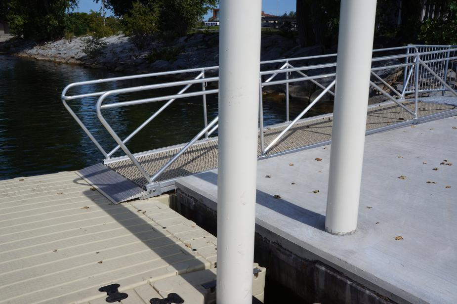 A ramp from a concrete dock down to a floating platform.