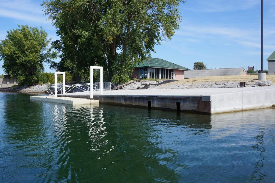 A concrete dock with two white metal u-shaped bars that connect to a floating platform.