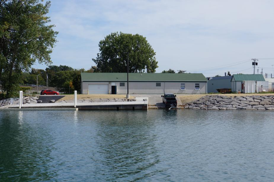 View from the water of a one-story building with a dock and ramp. It is similar to the previous picture except for the changes noted in the title text: the shoreline has neat stonework and the dock has a new concrete cap.
