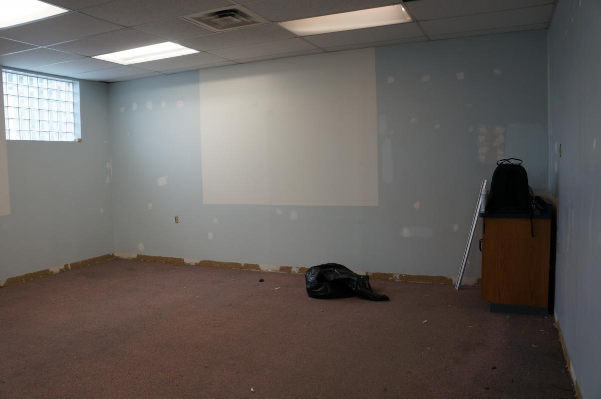 A room being renovated. There are putty patches on the wall and the base board has been removed. There is a bag of trash in the middle of the room.