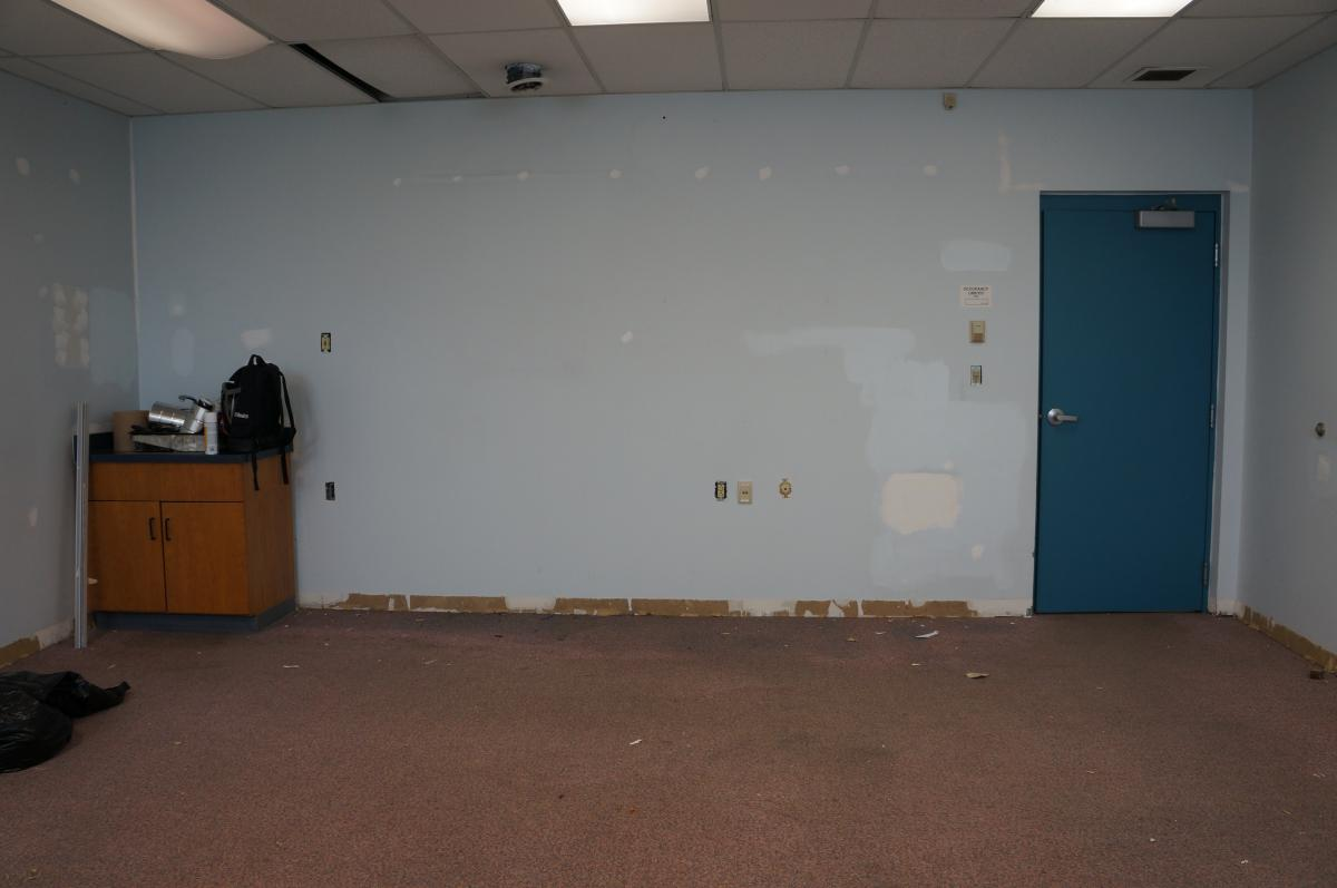 A room being renovated. There are putty patches on the wall and the base board has been removed. There is a small cabinet with a sink in one corner with a back pack and supplies on it.