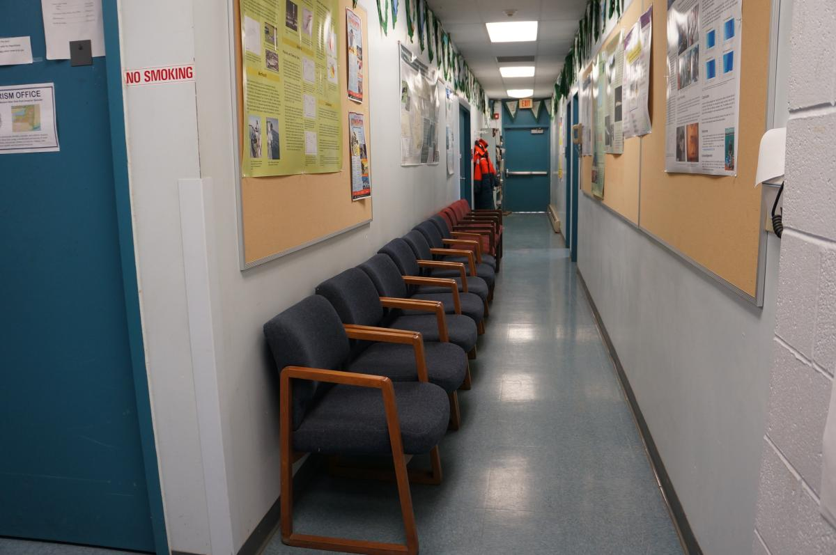 A line of chairs against the wall in a hallway.