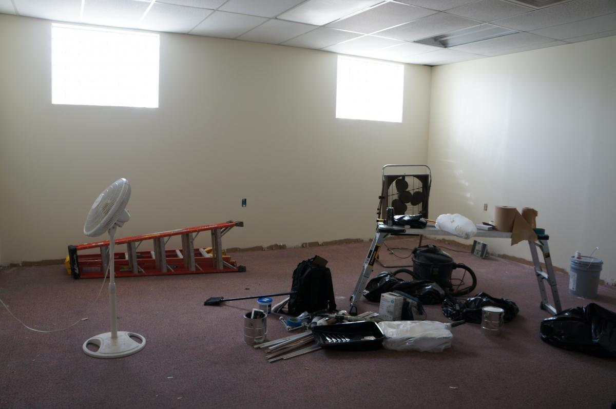 A room with some fresh paint on the walls. There are ladders, scaffolds, and painting supplies.