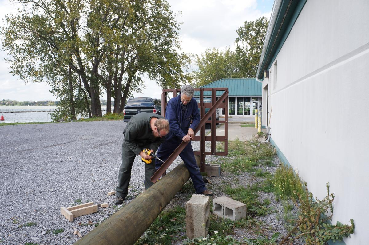 Two people attach a steel structure to a utility pole lying on the ground. One holds the steel while the other uses a drill.