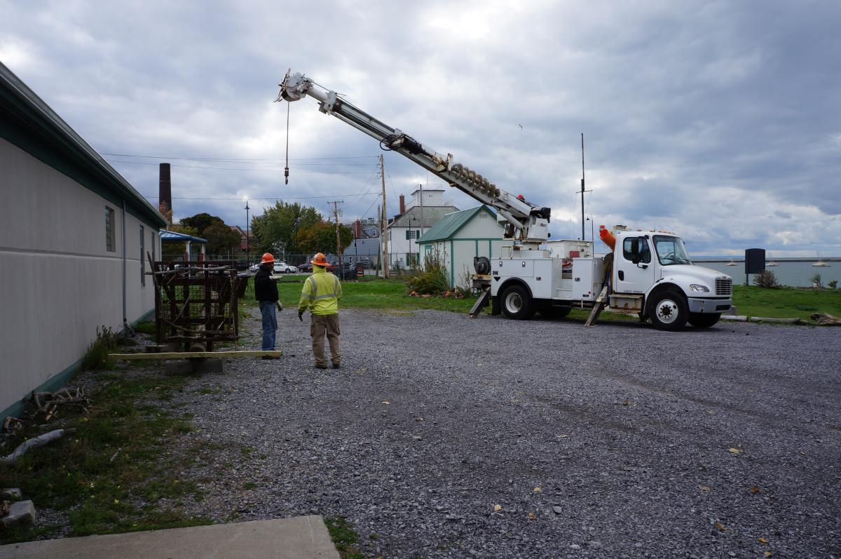 Two people in hard hats stand next to the osprey pole and a truck with a crane.