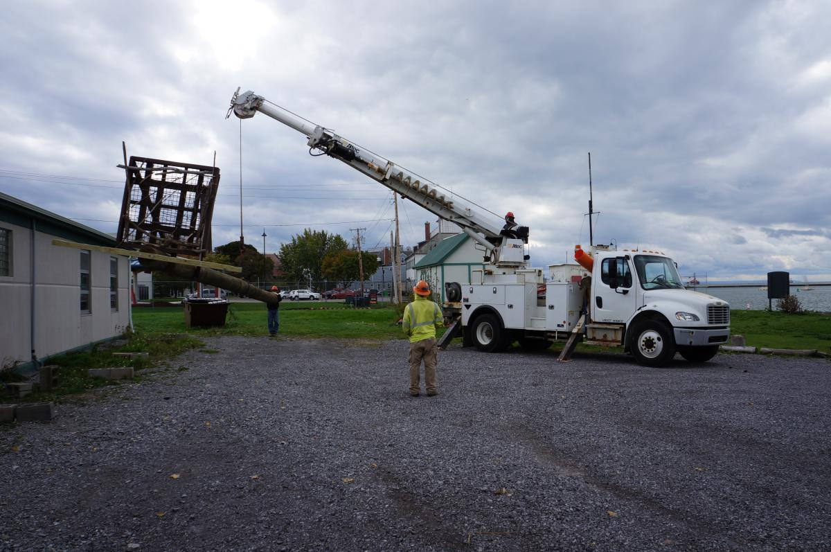A truck with a crane lifts the osprey pole off the ground while one person steadies one end and another person observes.