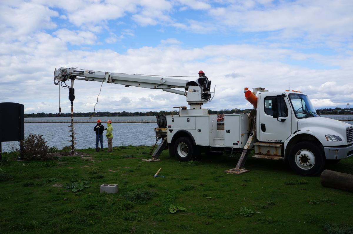 Two workers stand by while a third worker operates an auger on a truck to drill a hole by the waterfront.
