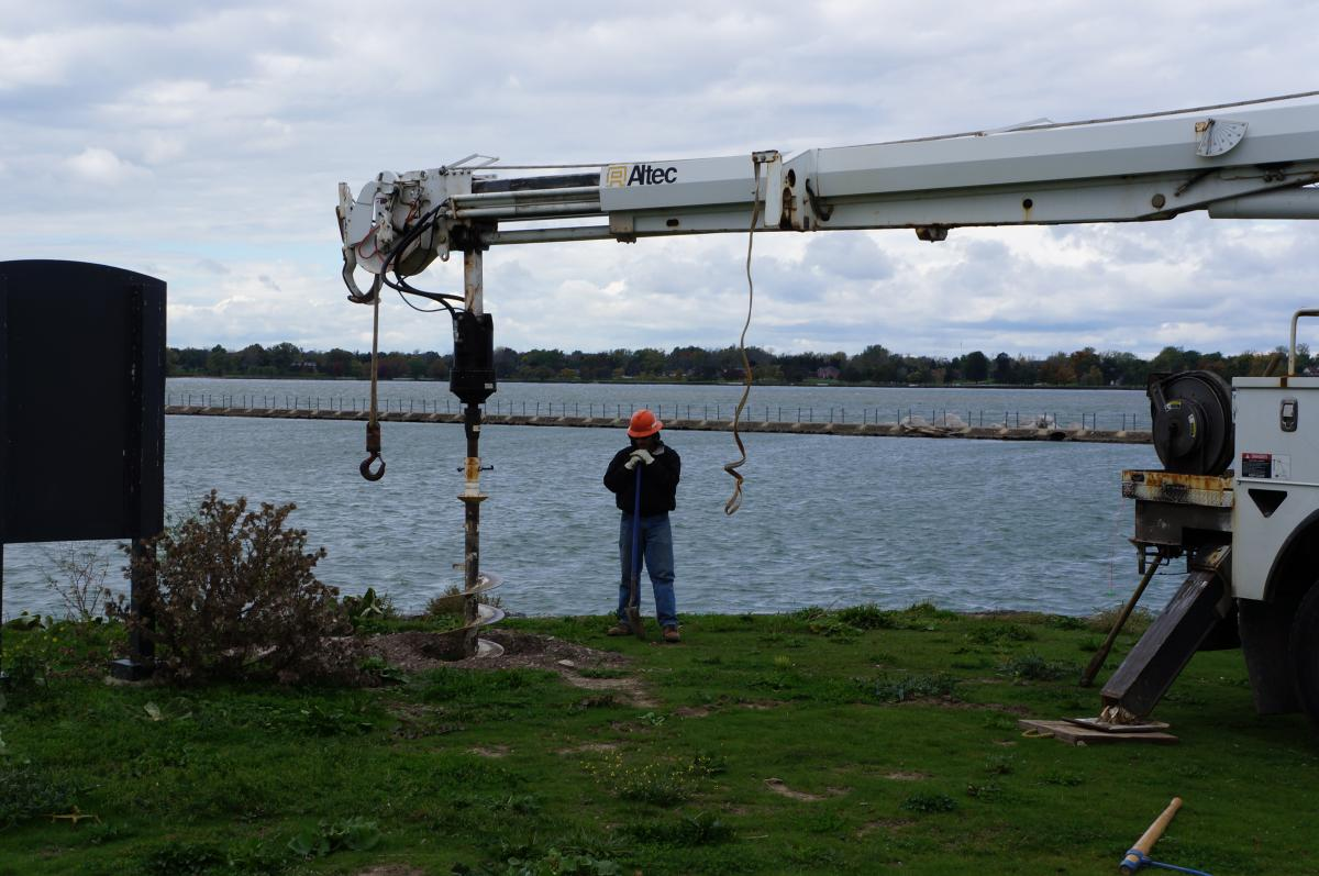 One worker watches an auger drill a hole in the ground near the waterfront.